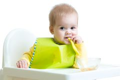 Baby child sitting in chair with a spoon Royalty Free Stock Photo