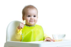 Baby child sitting in chair with a spoon Stock Photo