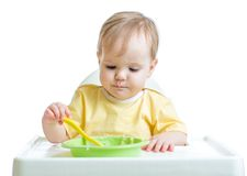 Baby child sitting in chair with a spoon Royalty Free Stock Image