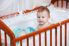 Baby in a children's bed Stock Image