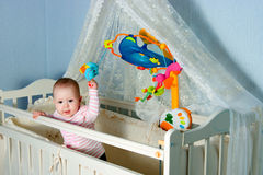 Baby in children's to a bed Stock Image