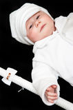Baby in christening clothes. Cute baby boy in white christening clothes with hat and candle, black background stock photo