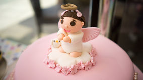Baby Christening Fondant Cake. Beautiful cake covered in fondant and topped with a gumpaste/sugarpaste topper of a baby angel on top Stock Image