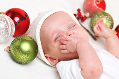 Baby with Christmas baubles Stock Image