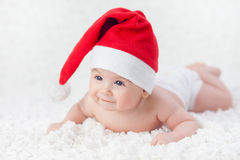 Baby in a Christmas cap. Baby lying in a Christmas cap Royalty Free Stock Photos