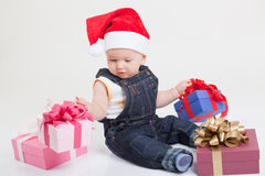 Baby with christmas cap sitting with gifts Royalty Free Stock Photo