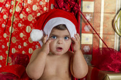 Baby with Christmas gifts. It is a baby with a santa hat surrounded by gifts Stock Photos