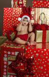 Baby with Christmas gifts. It is a baby with a santa hat surrounded by gifts stock images