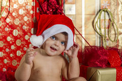 Baby with Christmas gifts. It is a baby with a santa hat surrounded by gifts Stock Photography