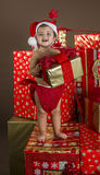 Baby with Christmas gifts. It is a baby with a santa hat surrounded by gifts Royalty Free Stock Images
