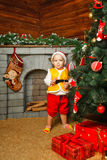 Baby Christmas gifts and Christmas tree. Child standing near Christmas tree beneath which lie gifts Royalty Free Stock Photography