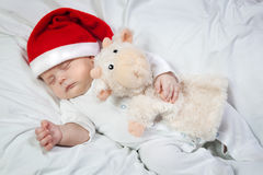 Baby in Christmas hat asleep hugging favorite toy Royalty Free Stock Photography