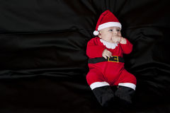 Baby Christmas Santa. Cute happy baby in red Christmas clothes  on  black background Stock Images