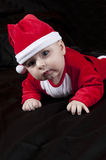 Baby Christmas Santa. Cute happy baby in red Christmas clothes  on  black background Stock Photography