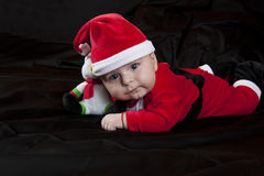 Baby Christmas Santa. Cute happy baby in red Christmas clothes  on  black background Royalty Free Stock Photography