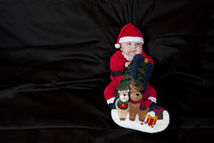 Baby Christmas Santa. Cute happy baby in red Christmas clothes  on  black background Stock Photos