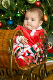Baby in a Christmas Sleigh. Serious Baby in a Christmas Sleigh stock photo