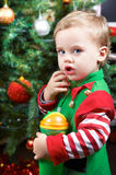Baby by the Christmas tree. One year old baby boy by the Christmas tree, dressed as an elf Stock Images
