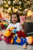 Baby and Christmas tree Stock Photos