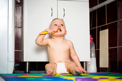 Baby cleaning teeth in bathroom Royalty Free Stock Photography