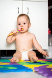 Baby cleaning teeth in bathroom Royalty Free Stock Image