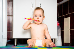 Baby cleaning teeth in bathroom Stock Images