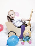 Baby climbing into dolls pram Stock Photo