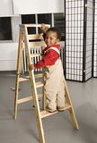 Baby climbing a ladder Stock Photo