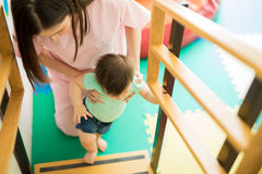 Baby climbing stairs with some help. Top view of a baby girl going up the stairs with the help of a children therapist in an early stimulation school royalty free stock image