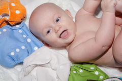 Baby with Cloth Diapers. A happy smiling baby lying next to a variety of cloth diapers stock photo