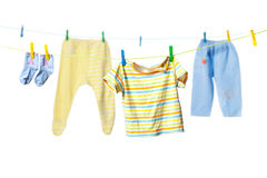 Baby clothes. Drying on a rope isolated on white background Royalty Free Stock Photos