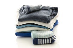 Baby clothes. A stack of baby clothes with socks on a white background stock photography