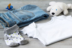 Baby clothes and accessories with white bear toy on a wooden background royalty free stock photo