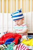 Baby among clothes. Baby age of 8 months among clothes stock photography