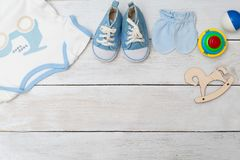Baby clothes and baby shoes for boy on wooden background. Copy s. Baby clothes and baby shoes for boy on wooden background. flat lay stock photo