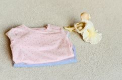Baby clothes. Beautiful Porcelain Figure of a Pretty Young Lady Ballet Dancer near a Baby clothes on a baby `s bed stock photo