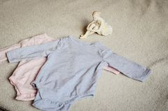 Baby clothes. Beautiful Porcelain Figure of a Pretty Young Lady Ballet Dancer near a Baby clothes on a baby `s bed royalty free stock images