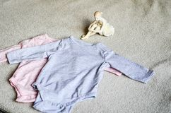 Baby clothes. Beautiful Porcelain Figure of a Pretty Young Lady Ballet Dancer near a Baby clothes on a baby `s bed stock images
