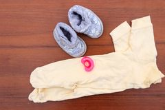 Baby clothes, booties and soother on wooden background. Kit for newborns Stock Images