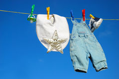 Baby clothes on clothesline. Baby clothes and accessories hanging on clothesline against blue sky royalty free stock photo