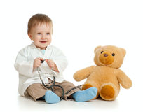 Baby with clothes of doctor and teddy bear. Adorable boy with clothes of doctor over white background Stock Image