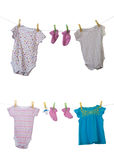 Baby clothes. Drying on a rope isolated on white background stock photo