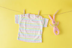 Baby clothes and easter rabbit on a clothesline Royalty Free Stock Photography