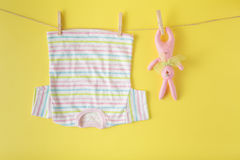 Baby clothes and easter rabbit on a clothesline Royalty Free Stock Image