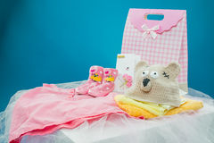 The baby clothes with a gift box. On blue background stock photo