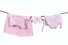 Baby clothes hang on clothesline stock photography
