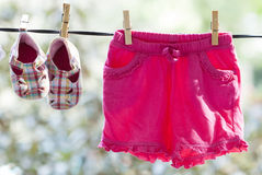 Baby clothes hanging Stock Images