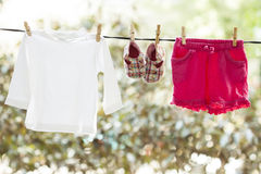 Baby clothes hanging. On the clothesline Stock Photos