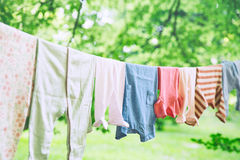 Baby clothes hanging on the clothesline. Baby cute clothes hanging on the clothesline outdoor. Child laundry hanging on line in garden on green background. Baby royalty free stock photography