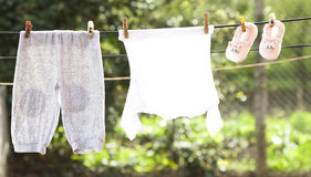 Baby clothes hanging on the clothesline. Small Baby clothes hanging on the clothesline royalty free stock image